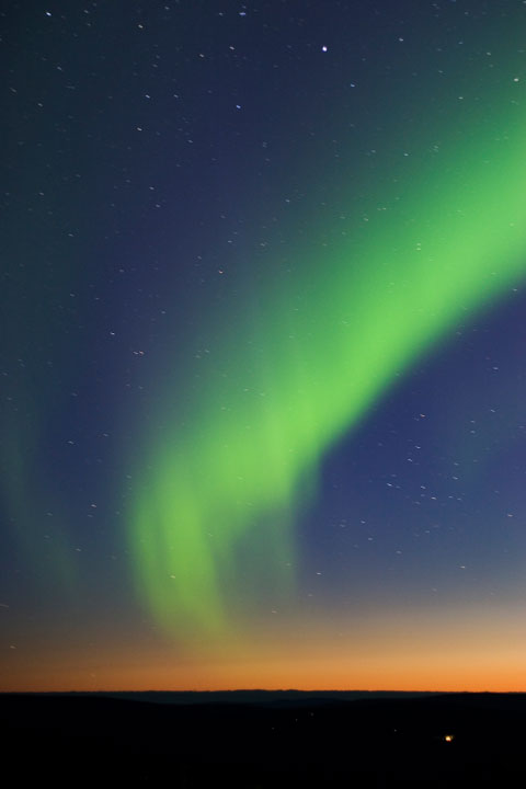 green northern lights at twilight